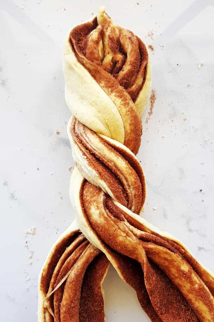 Twisting two strands of cinnamon roll dough to make a wreath