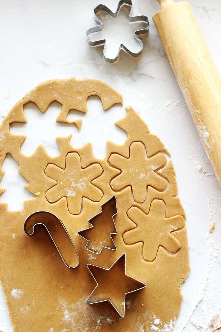 Gingerbread cookies being cut out with Christmas shaped cookie cutters