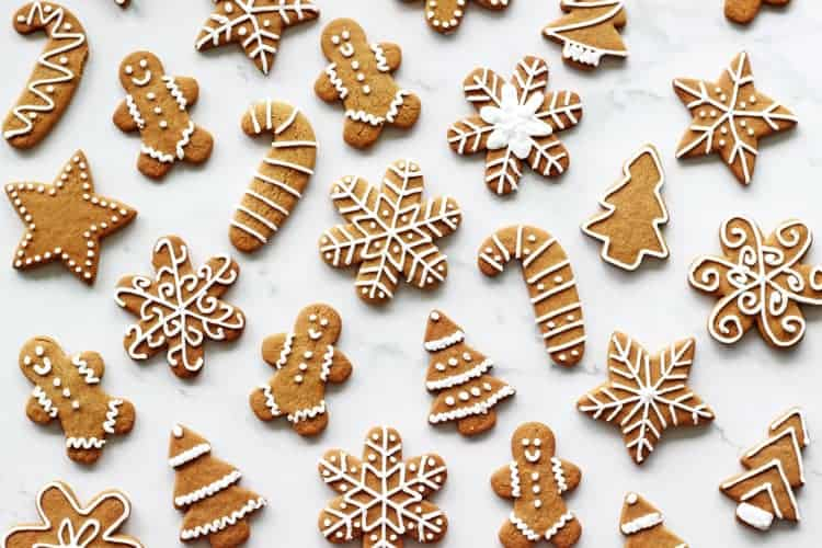 Decorated gingerbread cookies with royal icing in various shapes on a white background