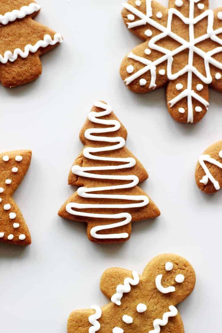 Christmas tree shaped decorated gingerbread cookie with royal icing on a white background