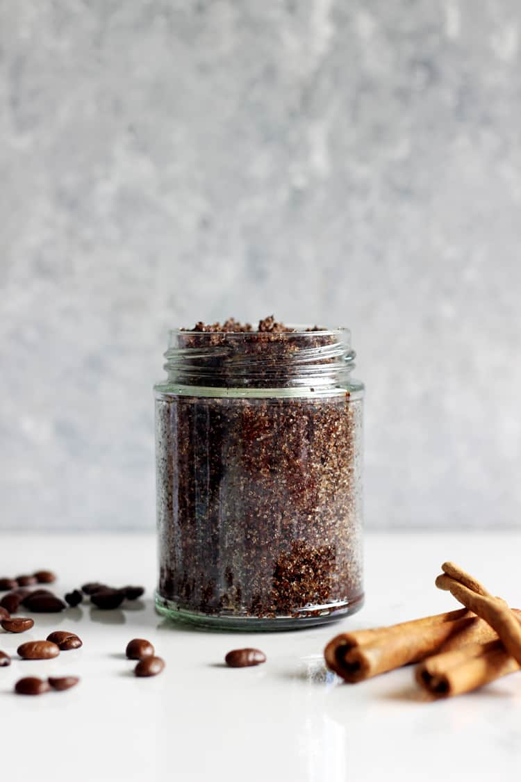 Coffee sugar scrub in a glass jar with coffee beans and cinnamon sticks on a white background