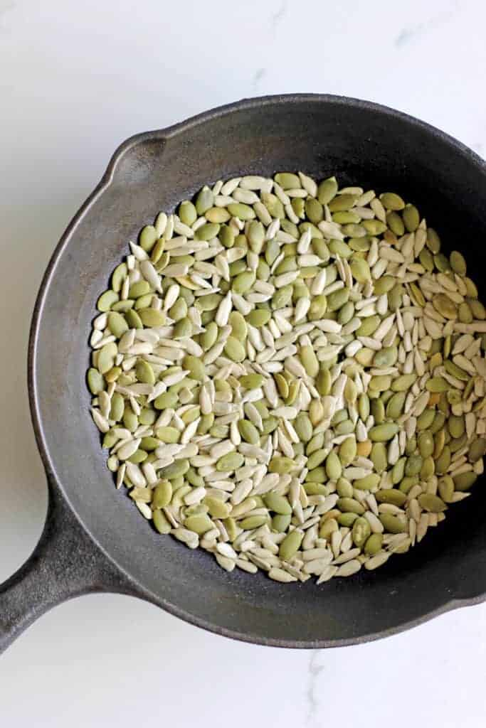 Frying pan with pumpkin and sunflower seeds being toasted