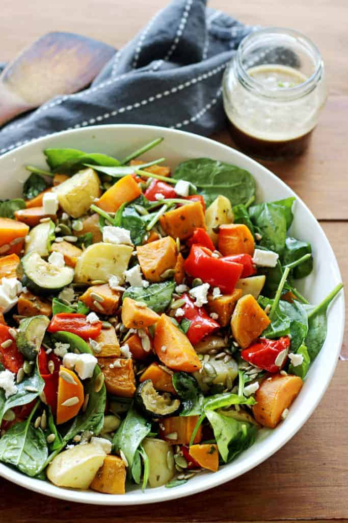 Roast Vegetable Salad on wooden table with serving spoon and dressing