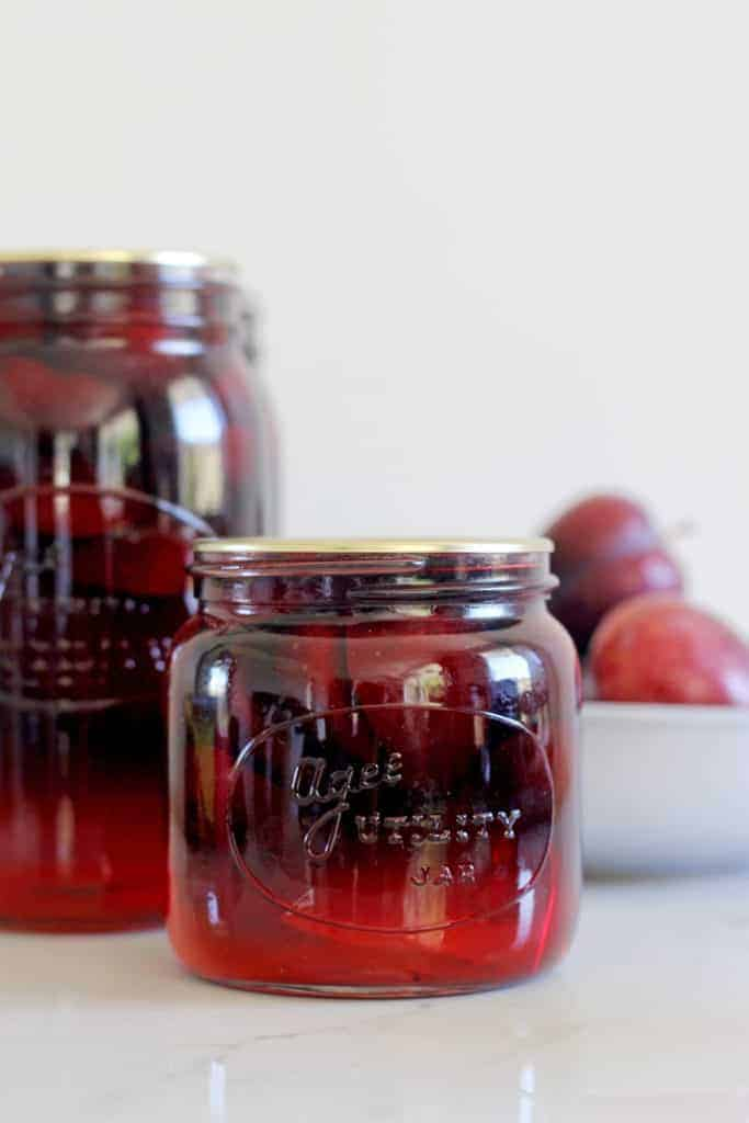 Sealed jars of bottled plums with bowl of plums in background