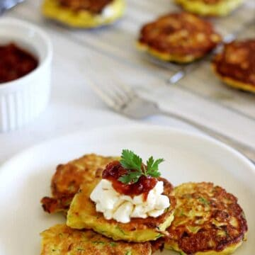 Plate with zucchini fritters topped with sour cream and more fritters in the background