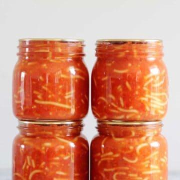 4 jars of homemade bottled spaghetti on a grey background