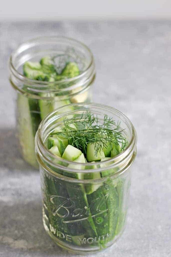 Jars of sliced pickling cucumbers and fresh dill on a grey background