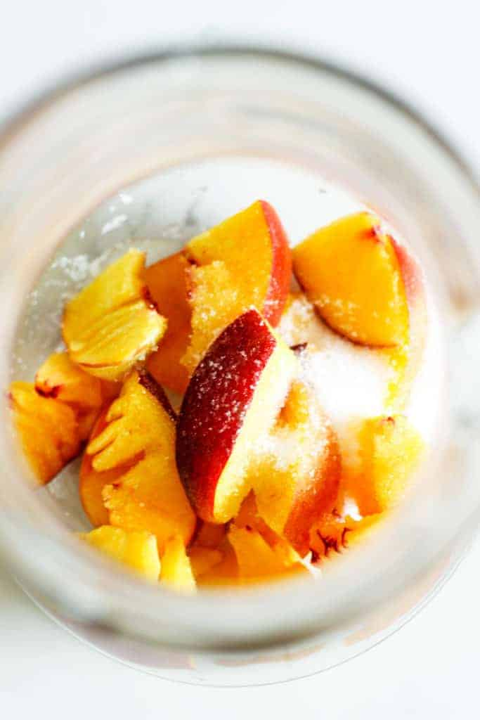 Overhead of peach slices and white sugar in a jug