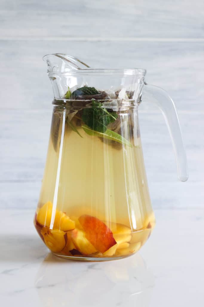 Cold brew peach iced tea in a glass jug at the beginning of the cold brew process