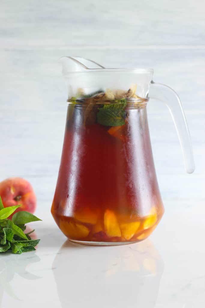 Cold brew peach iced tea in a glass jug at the end of the cold brew process