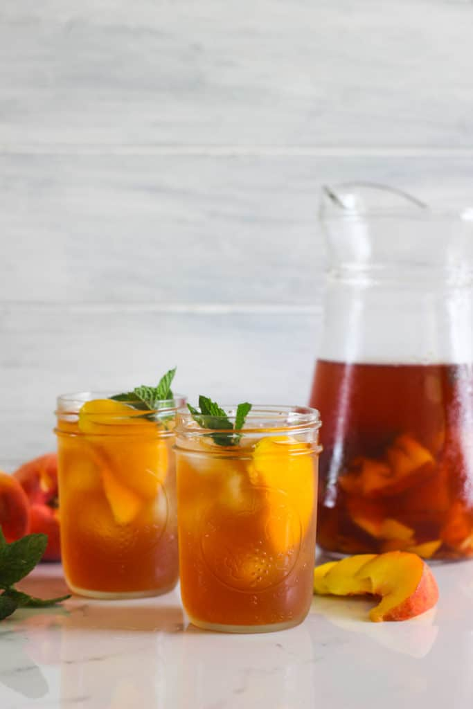 Jug of peach iced tea with 2 glasses and peaches in background