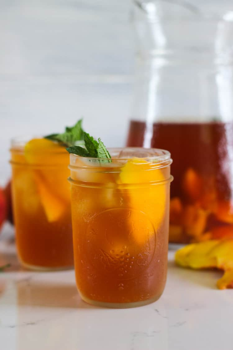 2 glasses of peach iced tea with jug in background