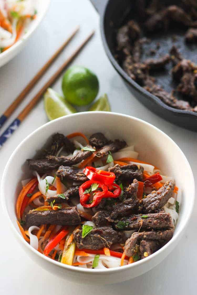 White bowl with beef noodle salad and chopsticks and limes in background