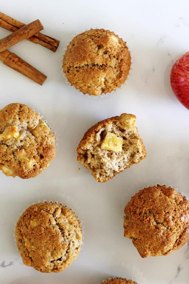 Spiced apple muffins on a white background with apples and cinnamon sticks