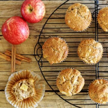 Spiced apple muffins on a wooden background with apples and cinnamon sticks