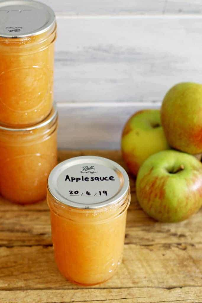 Jar of canned applesauce with apples on wooden background