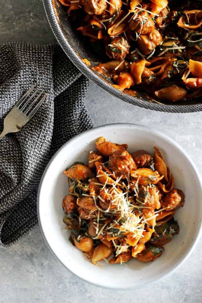 Bowl with sausage pasta and tea towel