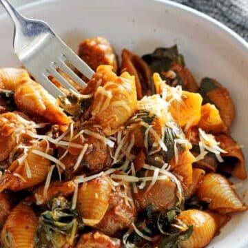 Fork in bowl of sausage pasta