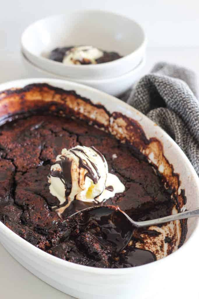 Chocolate self saucing pudding in white dish with bowl served up beside it
