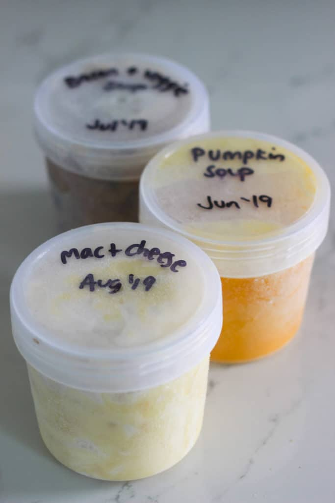 Individual plastic containers with soup and macaroni cheese