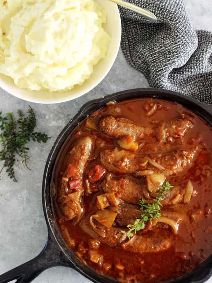 Pan of devilled sausages with mashed potato