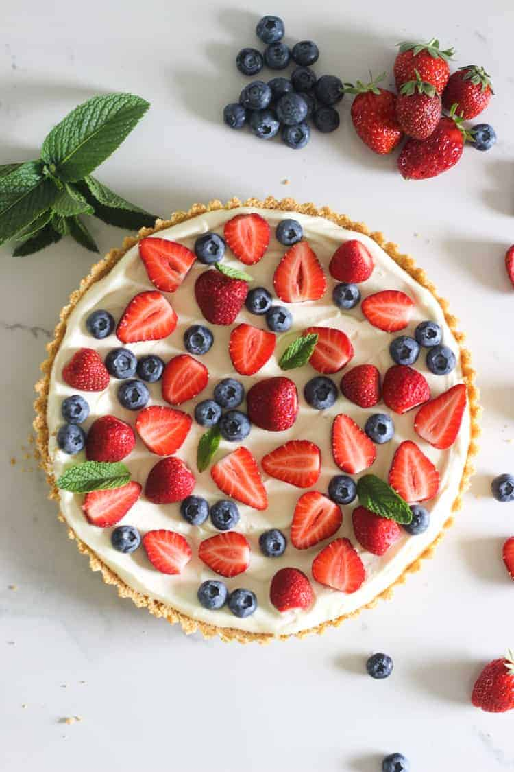 Summer berry tart on white marble background with strawberries and blueberries
