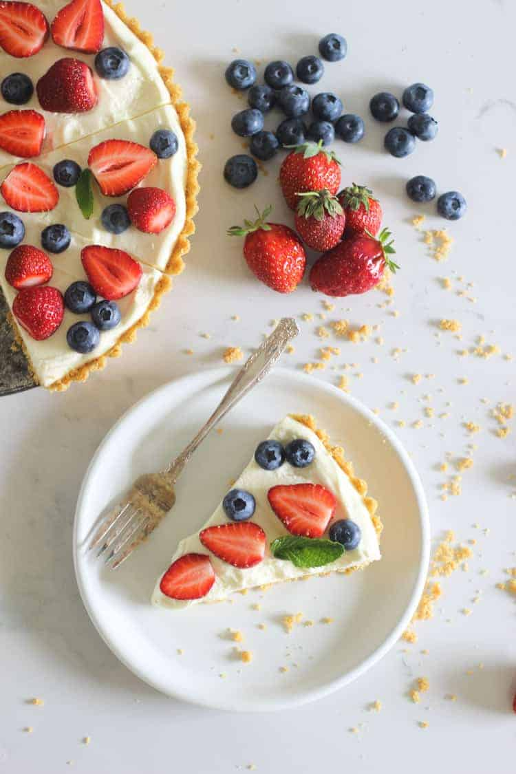 Slice of summer berry tart on white plate on marble background with strawberries and blueberries