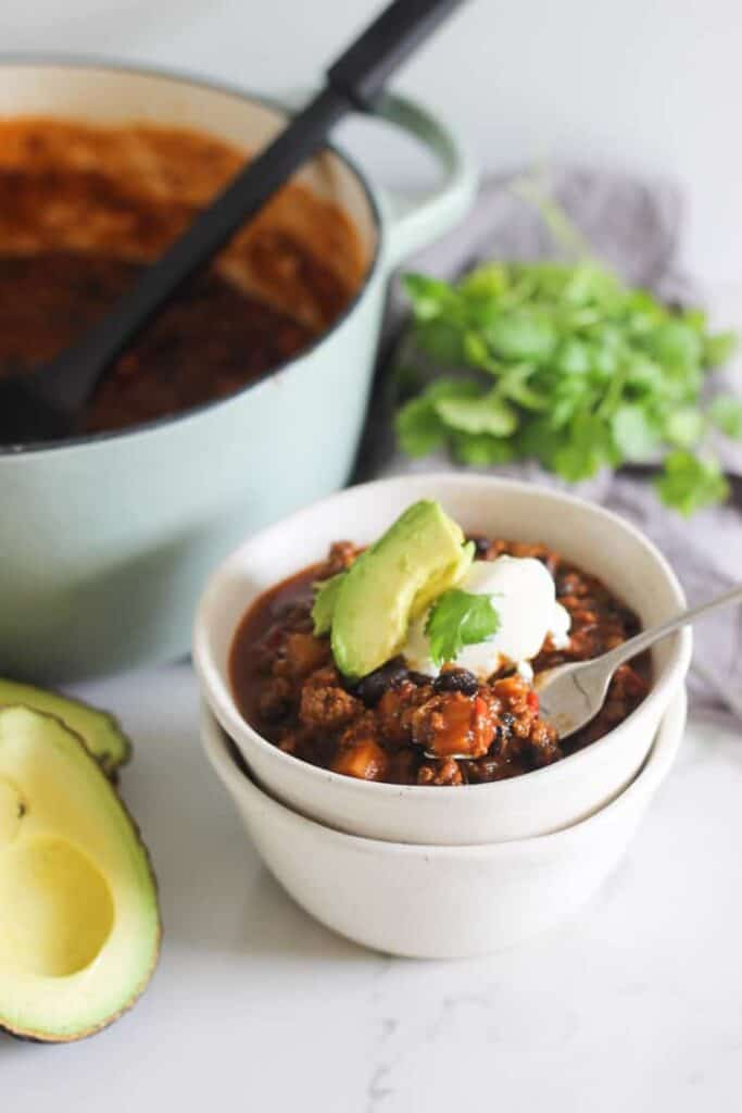 Bowl of chili with avocado, sour cream and pot in background