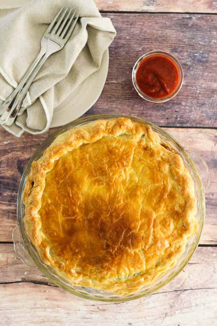 Baked mince and cheese pie with tomato sauce and forks