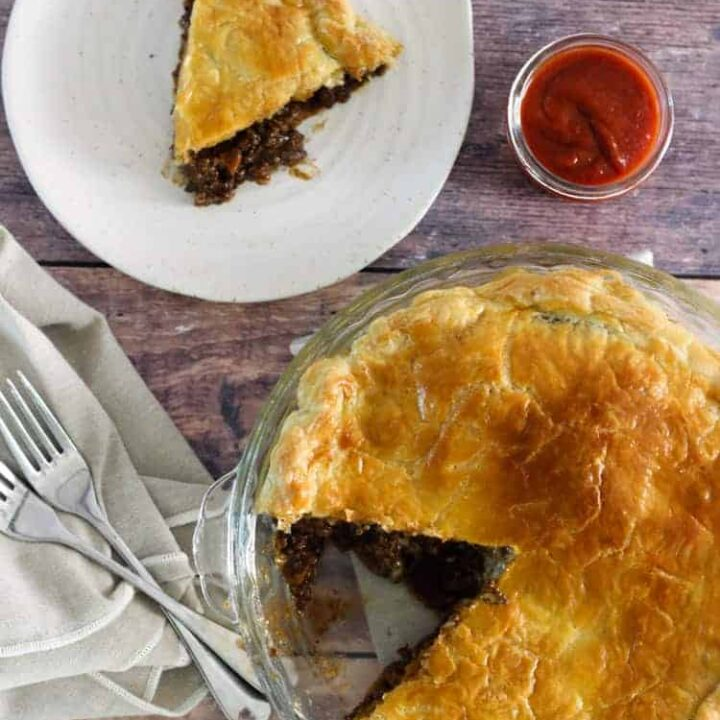 Baked mince and cheese pie with tomato sauce and forks with a slice on a plate