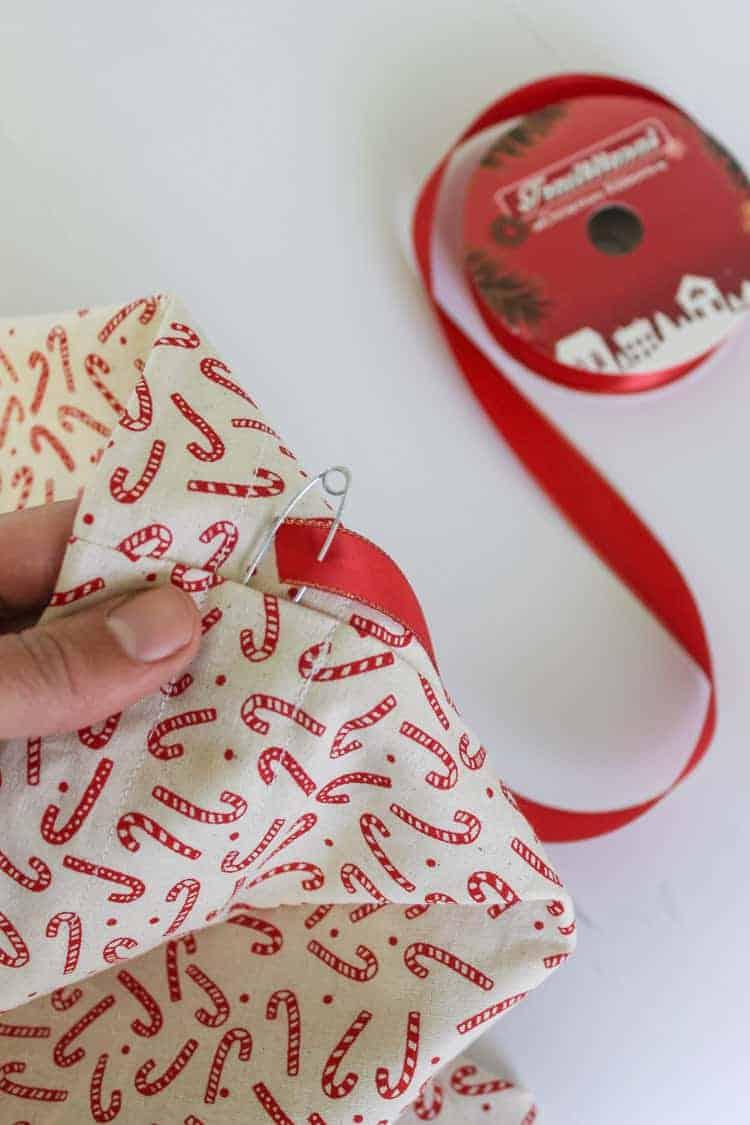 Red ribbon being threaded through a fabric Santa Sack