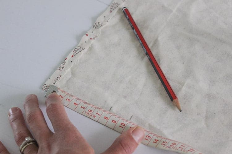 Piece of fabric with measurements for Santa Sack with measuring tape and pencil