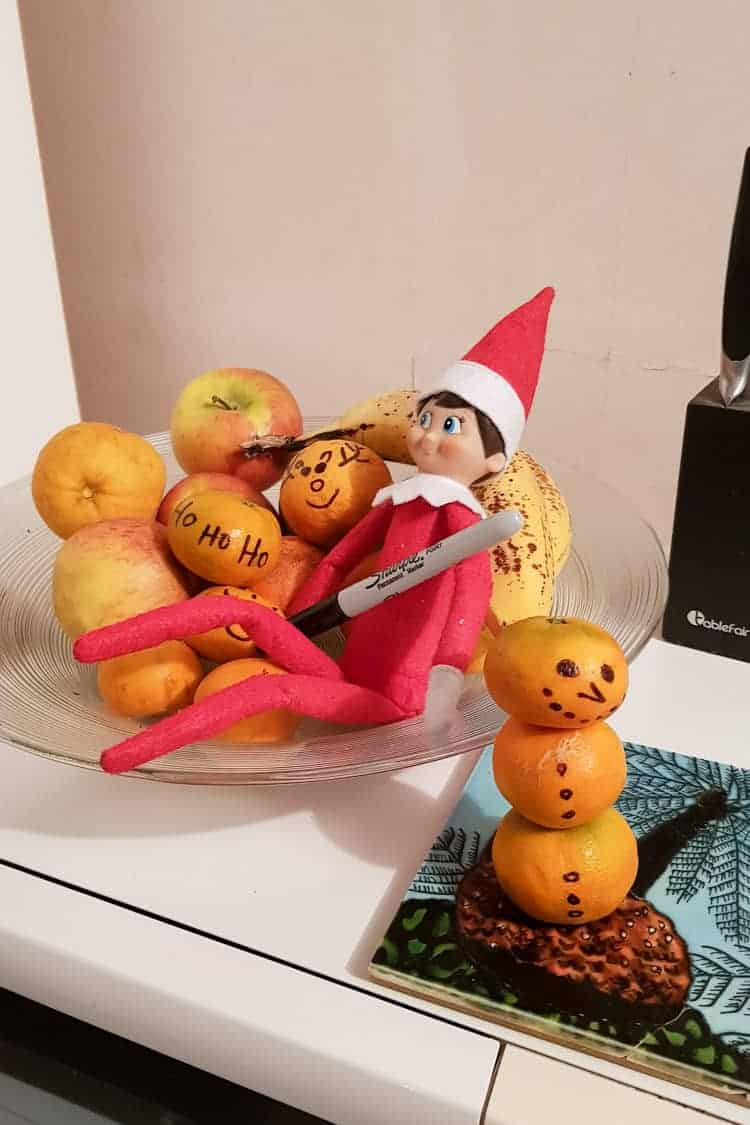 Elf on the shelf drawing on the fruit in the fruit bowl