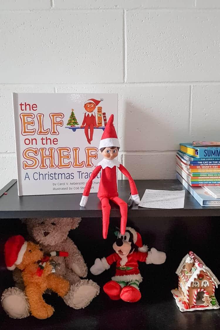 Elf on the shelf on a bookshelf with the book
