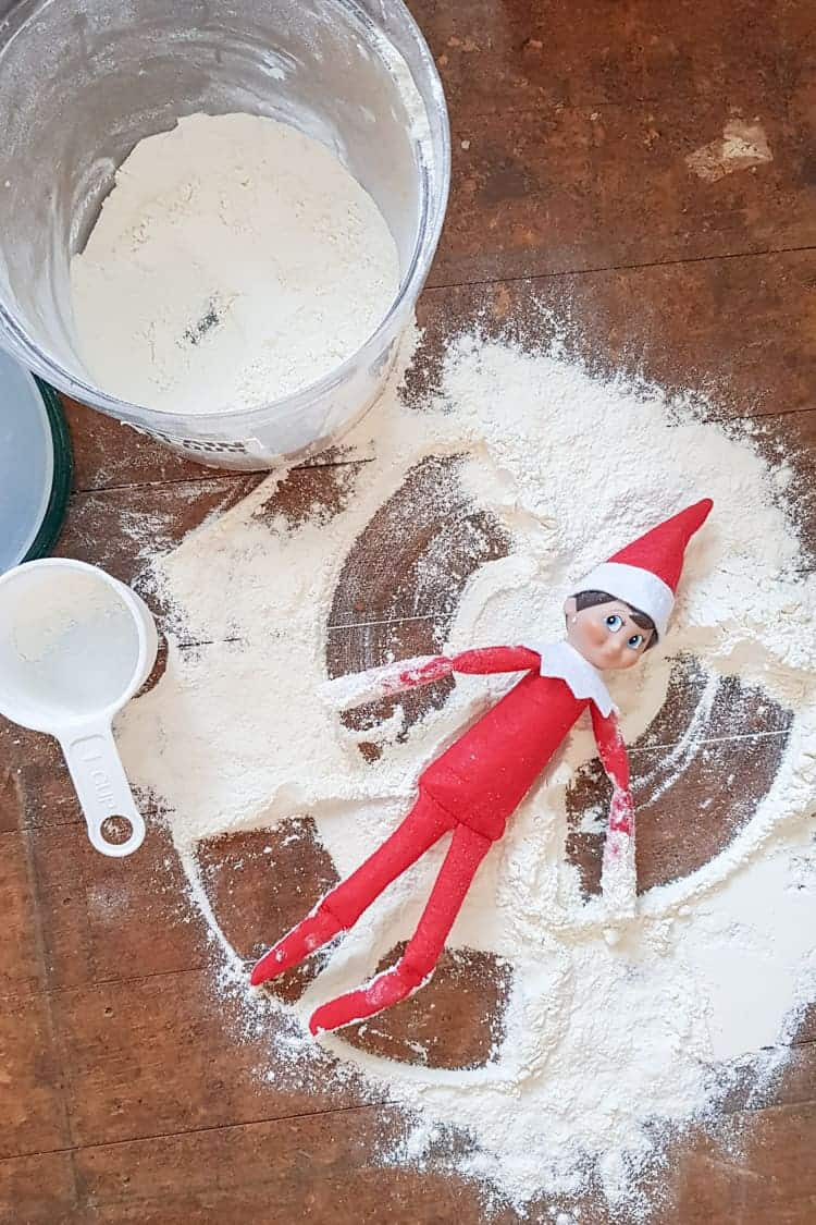 Elf on the shelf making a snow angel out of flour