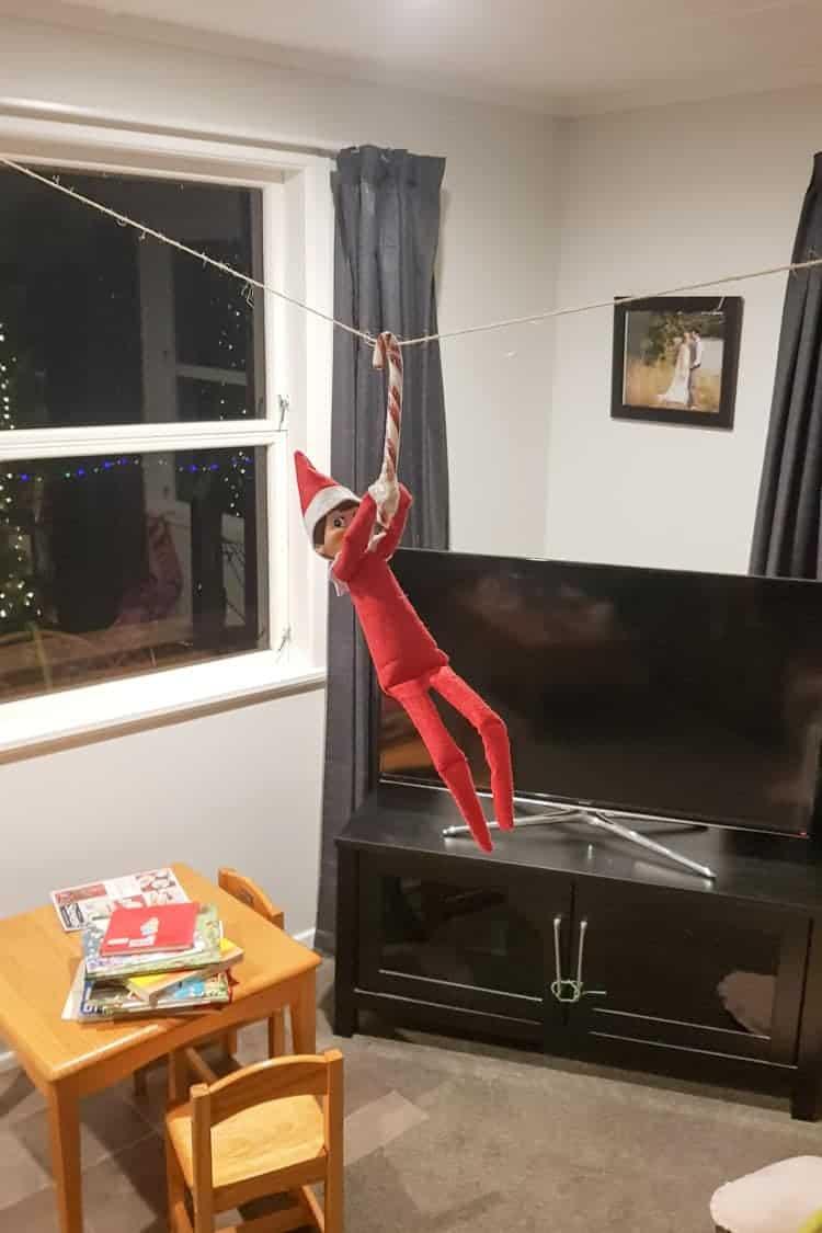 Elf on the shelf ziplining on a candy cane