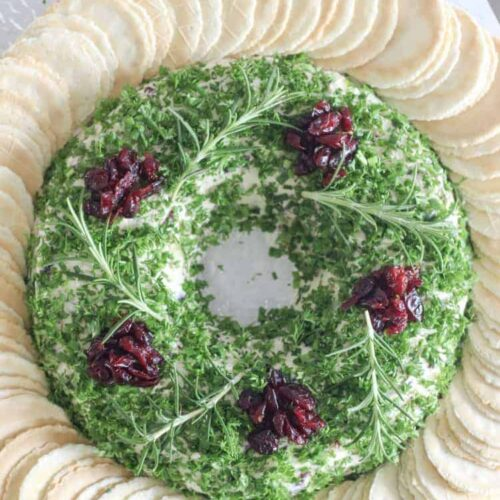 Christmas cheese ball wreath on serving plate with crackers and knife