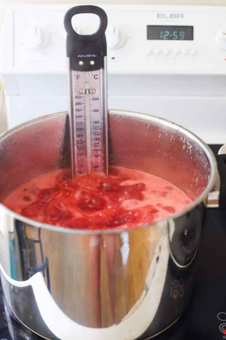 Pot of strawberry jam on stove with candy thermometer