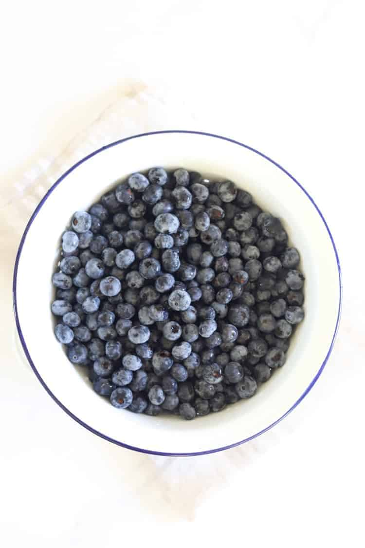 Colander of blueberries on a white background