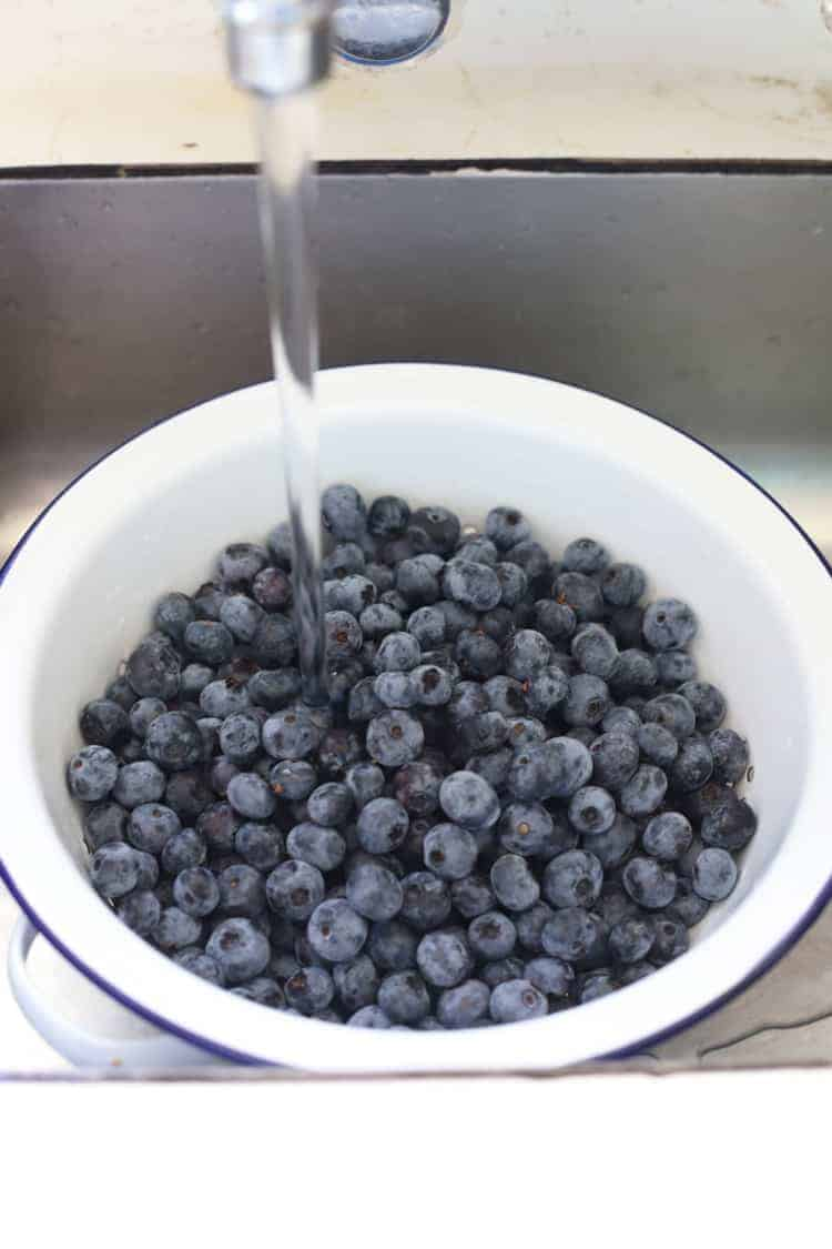 Colander of blueberries in the sink being washed
