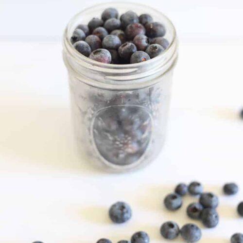 Ball mason jar of frozen blueberries on white background