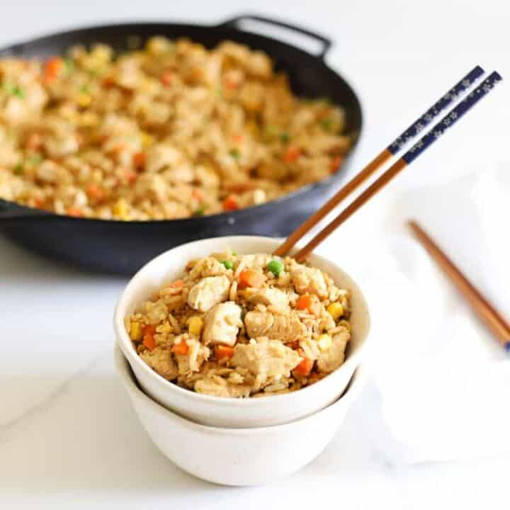 Chicken fried rice in a bowl with chopsticks and pan of fried rice in the background