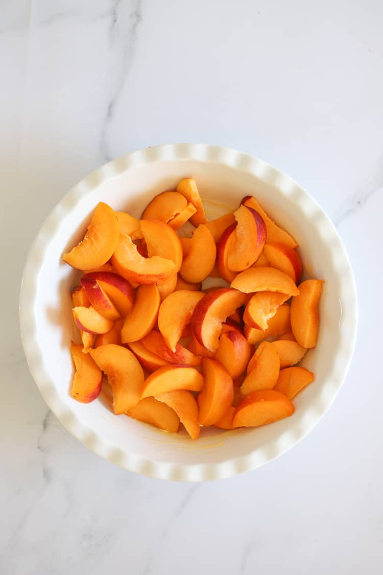 White pie dish filled with peach slices