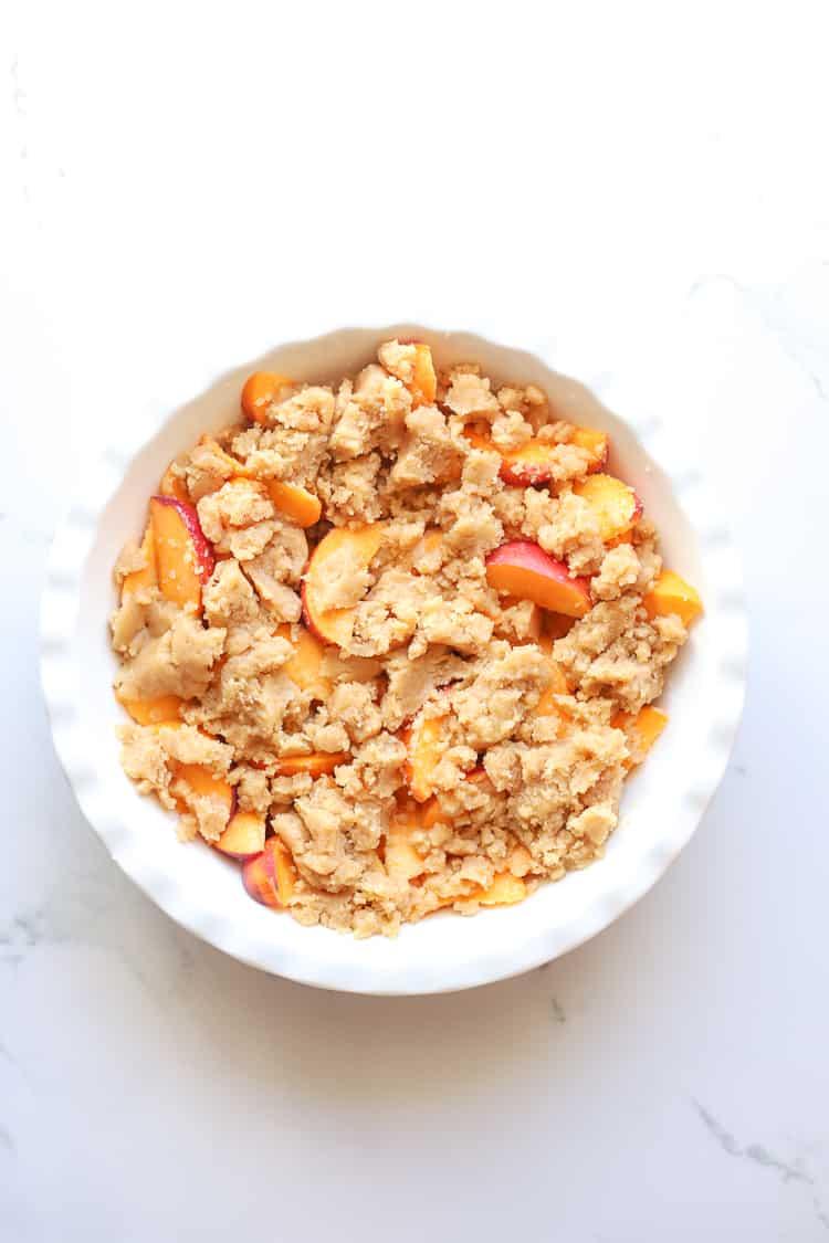 Unbaked peach cobbler in white pie dish