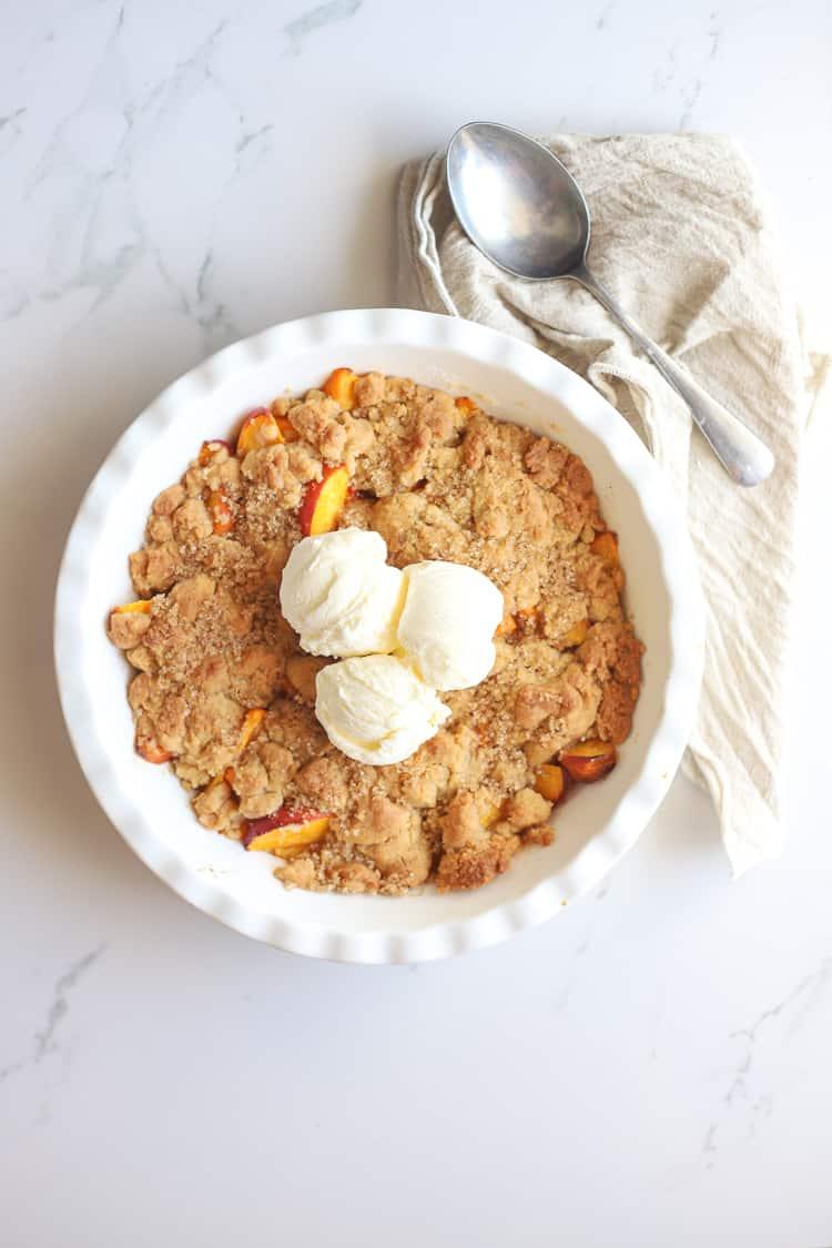 Peach cobbler with scooped vanilla icecream in a white pie dish